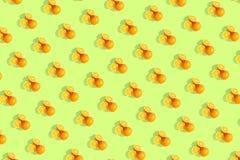 Апельсины на яркой покрашенной зеленой предпосылке Повторение картины, подготовка для настроения цитруса обоев стоковое изображение rf