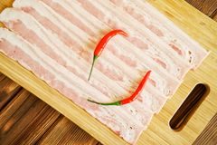 Аппетитные отрезанные части перцев бекона свинины и красного chili лежат на естественной деревянной поверхности еда здоровая Днев стоковое изображение