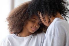 Африканская мать и дочь касаясь лбам имея близкое сильное соединение стоковая фотография
