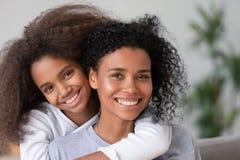 Африканская счастливые мать и дочь прижимаясь смотрящ камеру стоковые фотографии rf
