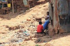 2 африканских женщины около хижин говорят среди отброса стоковое фото