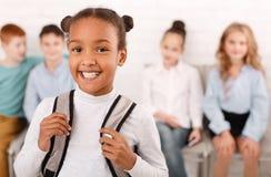 Афро-американская девушка школы с одноклассниками на предпосылке стоковые фотографии rf