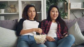 Афро-американские и азиатские молодые дамы наслаждаются комедией по телевизору дома, смеются, говорятся и едятся попкорном ослабл акции видеоматериалы
