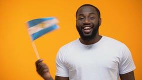 Афро-американский человек держа флаг Аргентины, торжество Дня независимости, праздник сток-видео