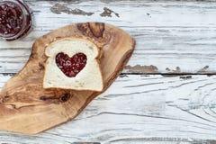 Арахисовое масло и сэндвич студня клубники с отрезка сердцем вне стоковое фото