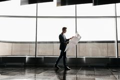 Архитектор в стильных одеждах держит лист с чертежом в его руке и беседах по телефону на предпосылке современного стекла стоковые изображения rf