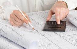 Архитектор используя калькулятор на архитектурноакустическом плане жилищного строительства светокопии стоковое фото