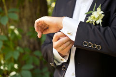 А cuff link. The young man clasps a cuff link on a shirt stock image