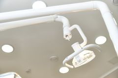 А glowing lamp over a dental chair close-up stock photo