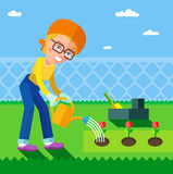 А woman who is watering the flowers in the garden in spring. Royalty Free Stock Photo