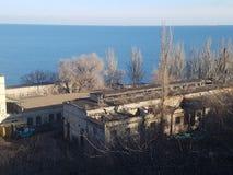 Аbandoned industrial buildings. Dilapidated, abandoned industrial buildings on the beach. Territory port of Odessa, Ukraine. January 2019 stock image