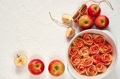 Аpple rose tart in the baking dish decorated with fresh sliced apples and cinnamon sticks. Vegetarian autumn pie on white table. Аpple rose tart in the stock images