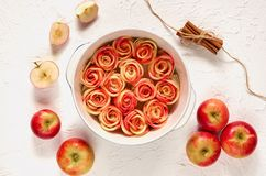 Аpple rose tart in the baking dish decorated with fresh sliced apples and cinnamon sticks. Vegetarian autumn pie on white table. Аpple rose tart in the stock image