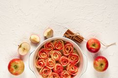 Аpple rose tart decorated with fresh sliced apples and cinnamon sticks. Vegetarian autumn pie on the white background. Top view. With copy space for text stock photos