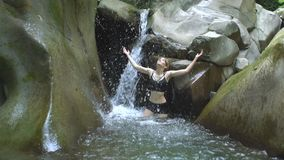 Аttractive girl in slow motion splashing clear water of mountain lake and looks to camera with small waterfall in green stock video footage