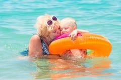 Бабушка и маленький заплыв внука в море Младенец в оживленном пестротканом круге каникула территории лета katya krasnodar стоковые фотографии rf