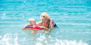 Бабушка и маленький заплыв внука в море Младенец в оживленном пестротканом круге каникула территории лета katya krasnodar стоковое изображение rf