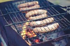 барбекю на нагом пламени/сосисках барбекю зажарено на меднике стоковое изображение