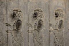 Барельеф показывает предохранители - воинов короля Старый сброс на стене загубленного города Persepolis Иран стоковые изображения