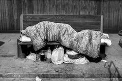 Бездомный человек, плохой бездомный человек или беженец спать на деревянной скамье на городской улице в городе с сумками одежд и  стоковая фотография rf