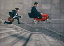 Безумные гонки бизнесмена с автомобилем для того чтобы выиграть конкуренцию против конкурентов Принципиальная схема успеха и конк стоковая фотография