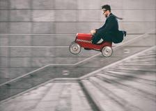 Безумный бизнесмен идет вниз с лестниц с автомобилем получить перед другими Принципиальная схема успеха и конкуренции стоковые фото