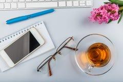 Белая таблица стола офиса с клавиатурой, телефоном, поставками сочинительства и цветками стоковая фотография rf