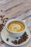 Белая чашка с черным кофе с молоком Пригорошня кофейных зерен на деревянном столе вертикальный взгляд напитка с кофе скопируйте к стоковые изображения rf