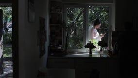 Беларусь, Минск - 26-ое июля 2018: невеста используя смартфон Женщина в платье свадьбы оставаясь с другой стороны окна акции видеоматериалы