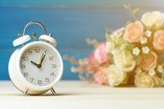 Белые будильник и цветки пинк и красная роза на деревянном столе и голубая предпосылка с космосом экземпляра для добавляют текст  стоковые фото