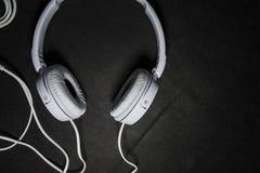 Белые большие наушники для слушать музыки Для телефона кожа Черная предпосылка Портативно устройства красивый и модный стоковые изображения rf
