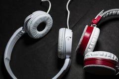 Белые большие наушники для слушать музыки Для телефона кожа Черная предпосылка Портативно устройства красивый и модный стоковые фото