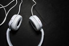Белые большие наушники для слушать музыки Для телефона кожа Черная предпосылка Портативно устройства красивый и модный стоковое изображение
