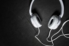 Белые большие наушники для слушать музыки Для телефона кожа Черная предпосылка Портативно устройства красивый и модный стоковое фото rf