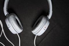 Белые большие наушники для слушать музыки Для телефона кожа Черная предпосылка Портативно устройства красивый и модный стоковая фотография rf