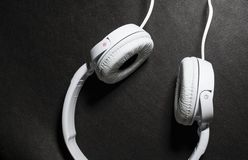 Белые большие наушники для слушать музыки Для телефона кожа Черная предпосылка Портативно устройства красивый и модный стоковое фото