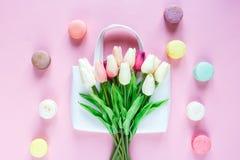 Белые косметические сумка и тюльпаны, macaroons на розовой предпосылке Праздничная предпосылка на день матерей, стоковые фото