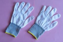 Белые перчатки работы на розовой предпосылке прозодежды и формы Предохранение от руки стоковое фото