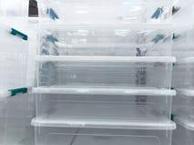 Белые пищевые контейнеры прозрачной пластмассы на полке в магазине стоковая фотография