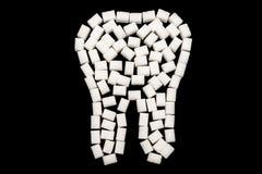 Белый зуб сделанный из кубов сахара против черной предпосылки стоковое фото rf