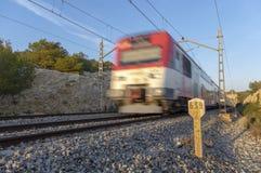 Белый и красный короткий поезд расстояния в движении выходя тоннель и с kilometric дорожным знаком стоковая фотография