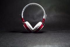 Белый с красными большими наушниками для слушать музыки кожа Черная предпосылка Портативно устройства красивый и модный стоковое фото