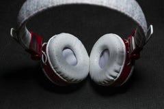 Белый с красными большими наушниками для слушать музыки кожа Черная предпосылка Портативно устройства красивый и модный стоковое фото rf