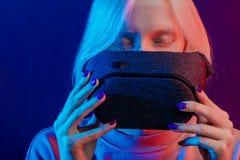 Белокурая девушка держа стекла VR, изолированную голубую предпосылку стоковое изображение rf