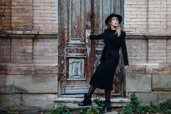 Белокурая девушка с длинными волосами, в черном пальто в шляпе, стойки на предпосылке дома кирпича винтажной античной старой дере стоковая фотография