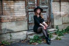 Белокурая девушка с длинными волосами, в черном платье в шляпе, сидит на шагах на предпосылку винтажной античной старой деревянно стоковые фотографии rf