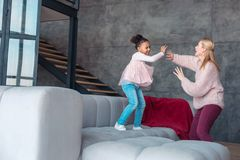 Белокур-с волосами мама и ее танцы и смеяться приемного ребенка стоковое изображение