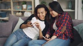 Беспечальные молодые женщины имеют потеху со смартфонами смотря экран, смеясь и говоря наслаждающся интернетом и акции видеоматериалы