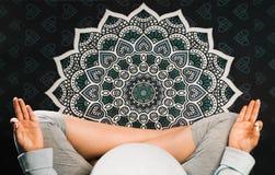 Беременная женщина сидя в положении лотоса на циновке и размышлять йоги мандалы Взгляд сверху стоковая фотография