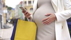 Беременная женщина с хозяйственными сумками чувствуя сужения, вызывая 911, роды стоковое фото rf